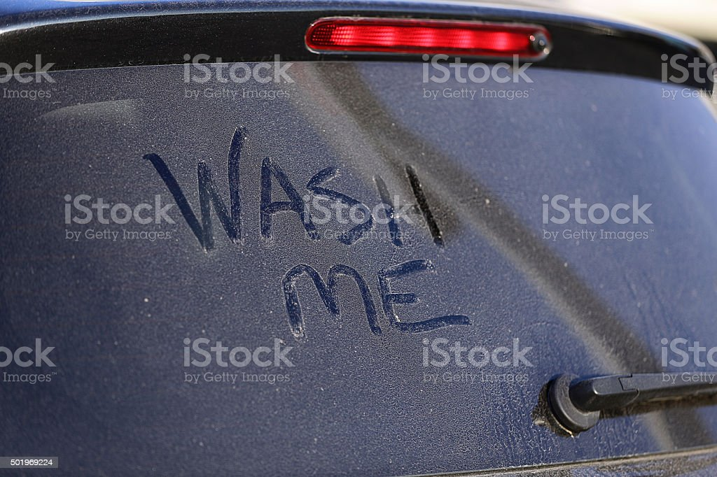 Dirty car window and wash me sign stock photo
