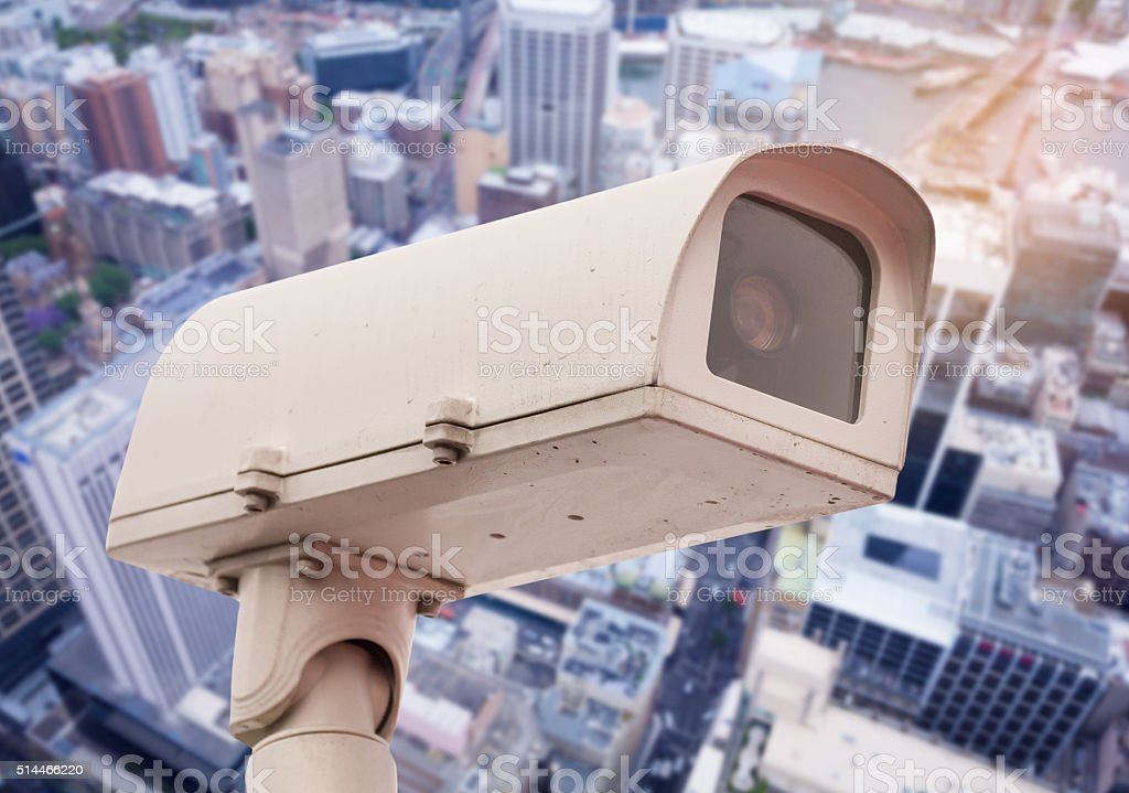 Dirty CCTV security camera with blurred office building background. stock photo