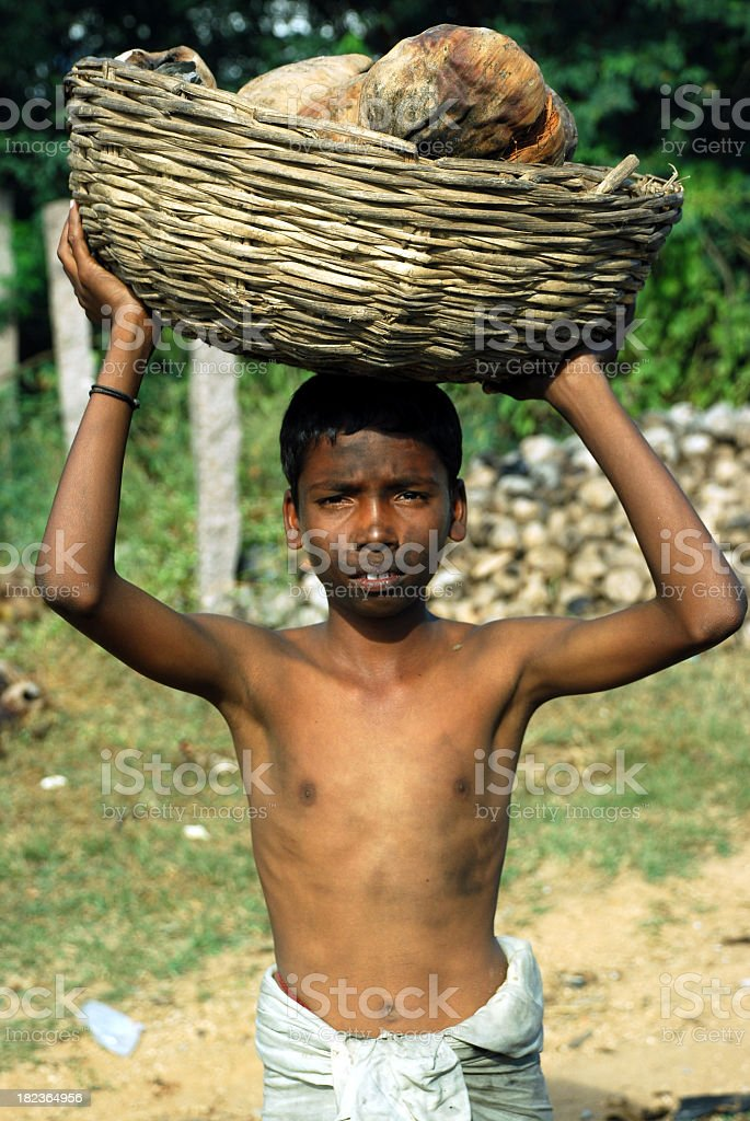 Dirty child carrying items gathered in third world country stock photo