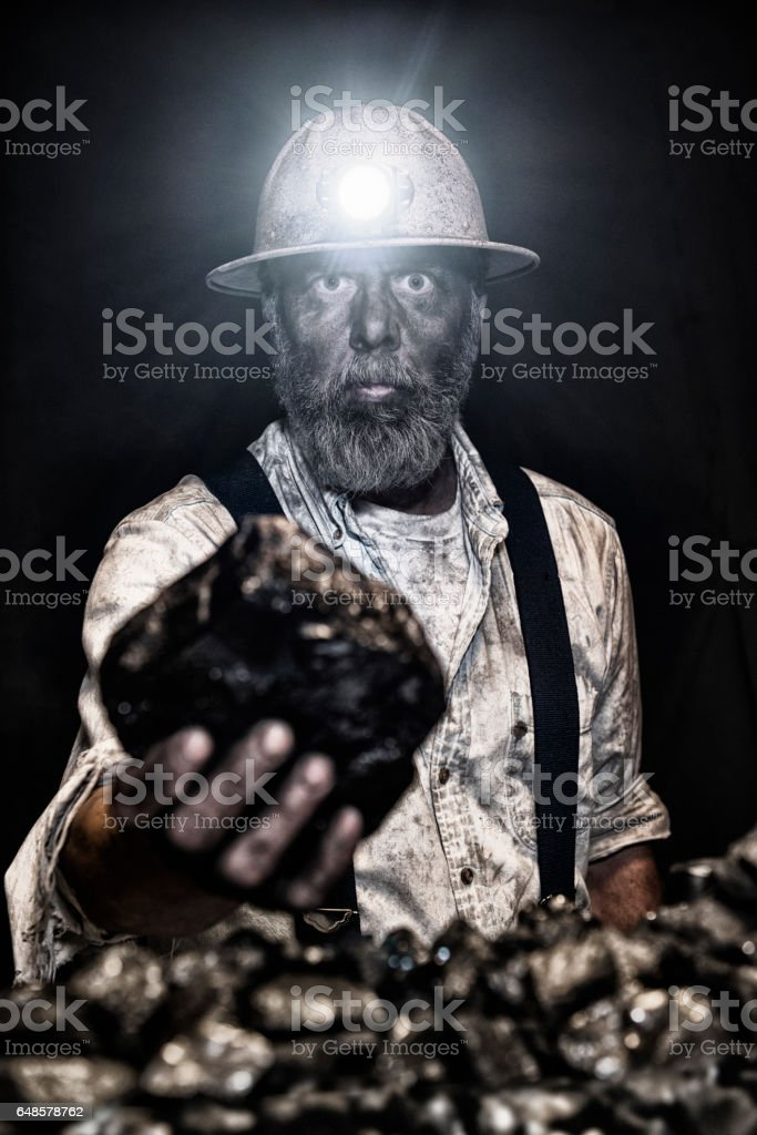 Dirty coal miner wear hardhat holding large piece of coal stock photo