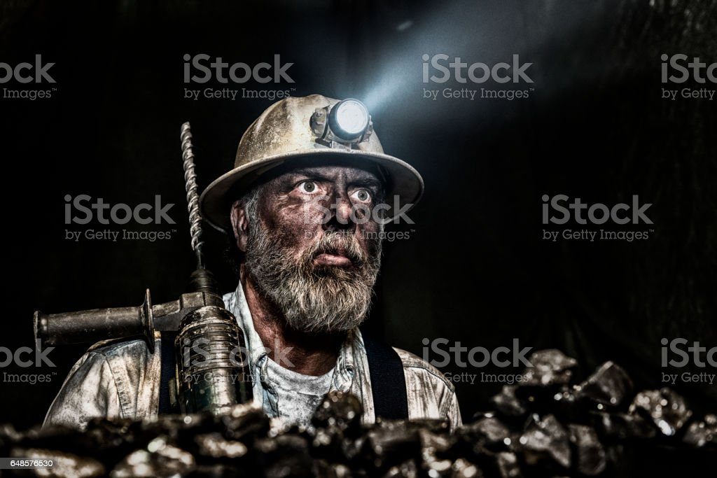 Dirty coal miner wear hardhat with a hammer drill stock photo