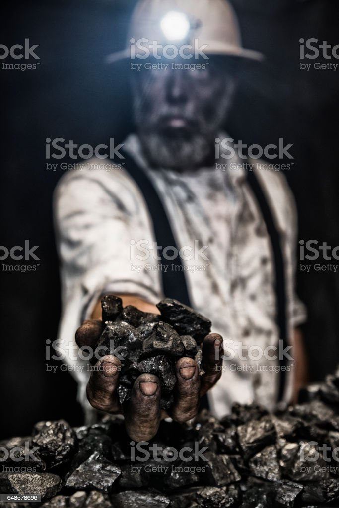 Dirty coal miner wear hardhat with handful of coal stock photo