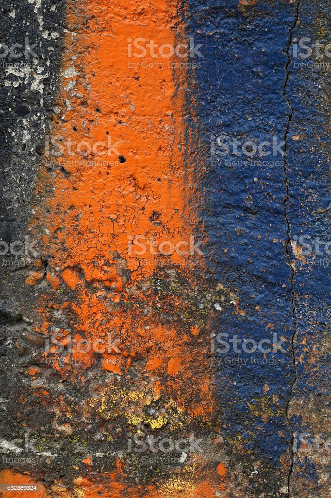 Dirty concrete wall with orange and blue paint stock photo