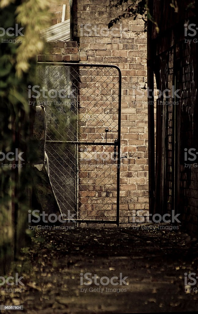 Dirty dark alley an open gate with metal chain mesh stock photo