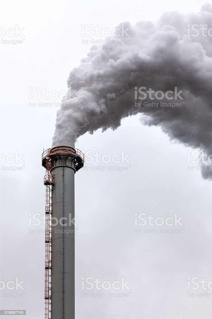 Dirty dark smoke clouds from a high industrial chimney stock photo