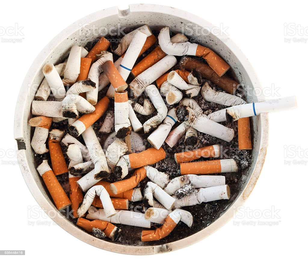 Dirty disgusting burnt cigarette filled ash tray, clipping path stock photo