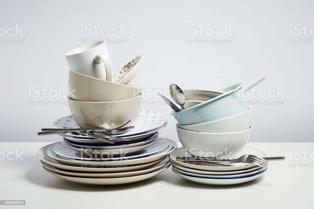 Dirty dishes pile needing washing up on white background stock photo
