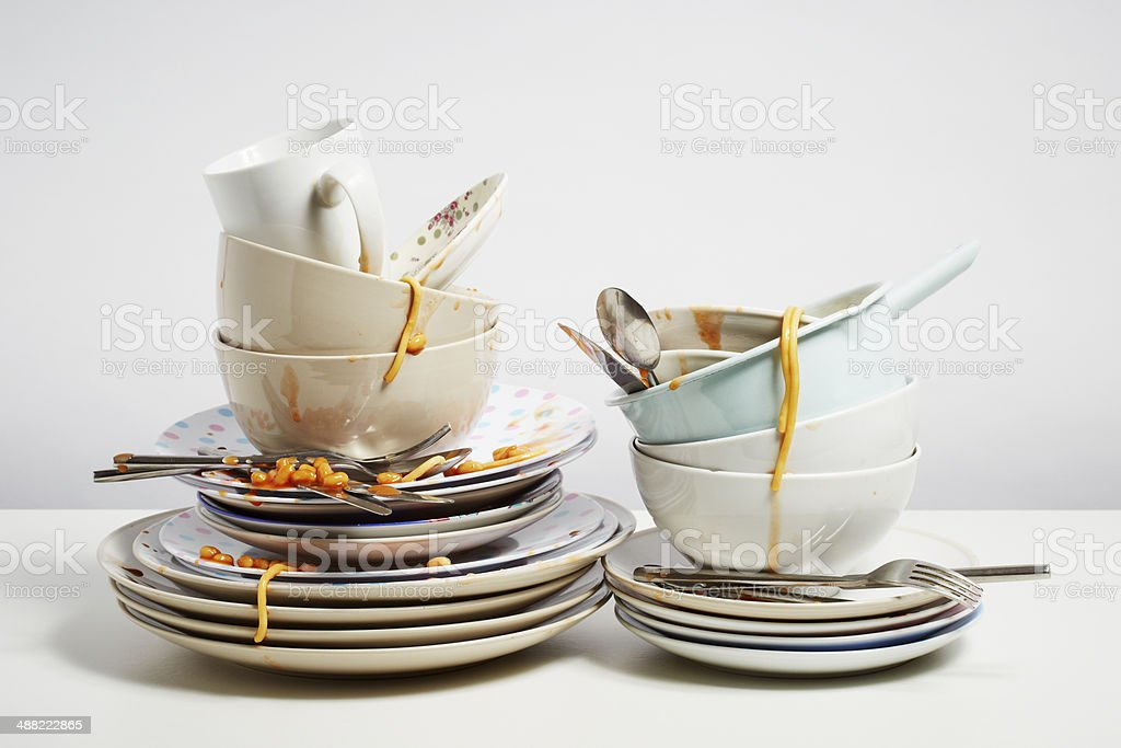 Dirty dishes pile needing washing up on white background stock photo
