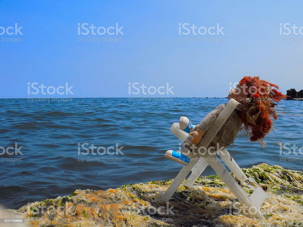 dirty doll is sitting on the beach stock photo