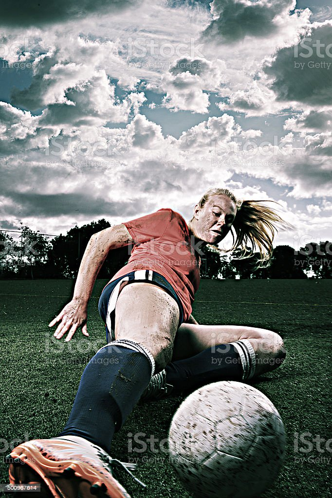 Dirty Female Soccer Player Sliding for the Ball stock photo