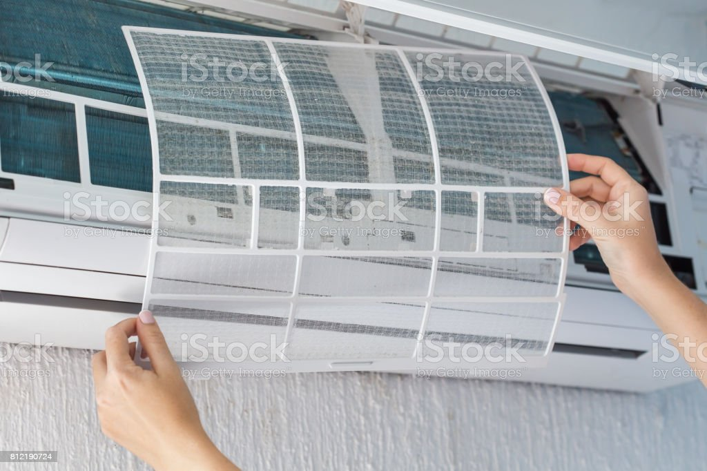 Dirty filter of air conditioner in female hands stock photo