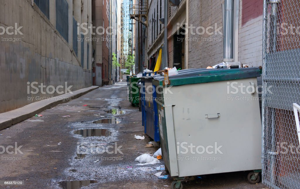 Dirty filthy back alley with dumpsters and garbage trash stock photo