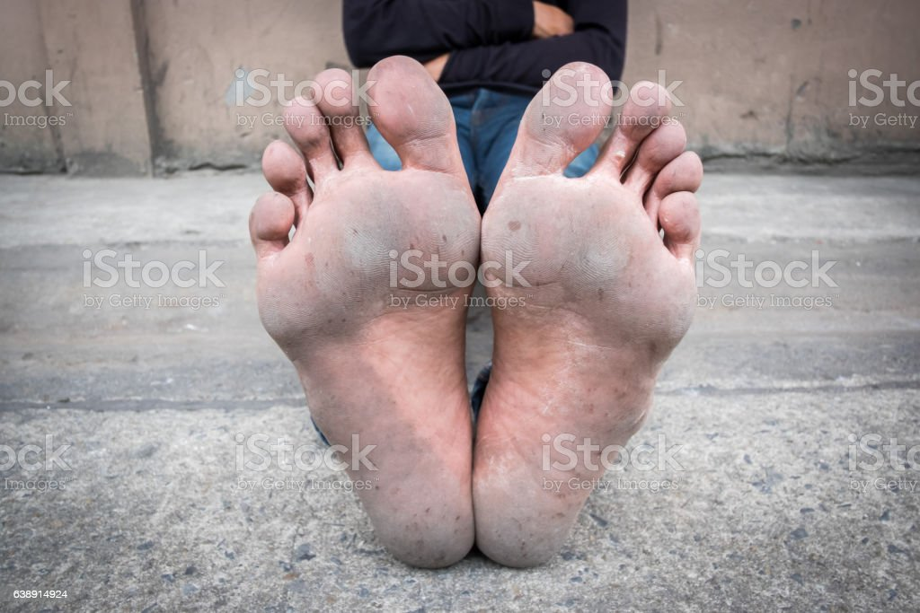 Dirty foot of a man sitting on old concrete floor. stock photo