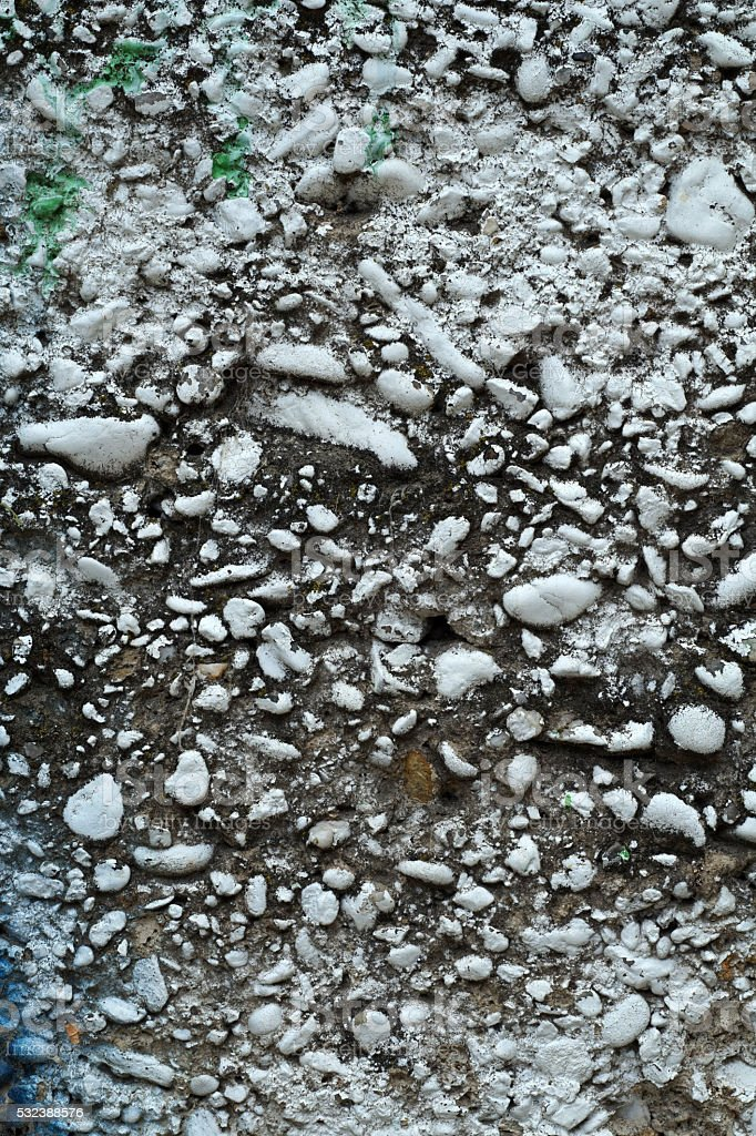 Dirty grey concrete wall with colored stones 1 stock photo