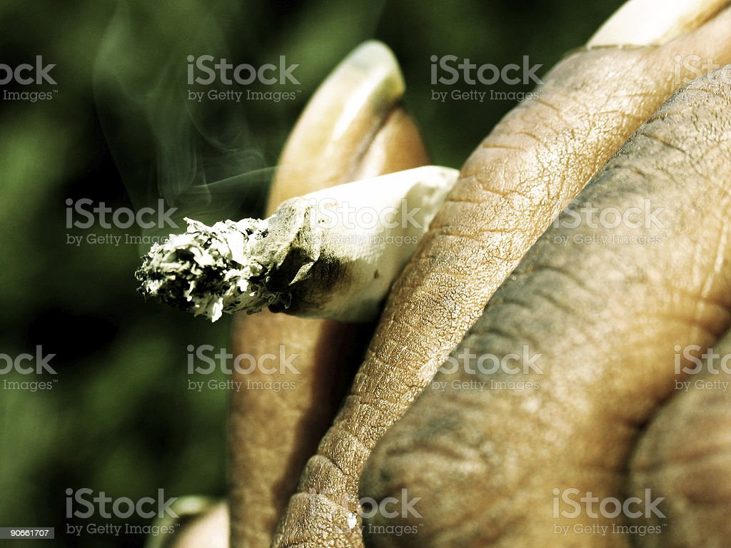 Dirty Hand Holding Rolled Cigarette royalty-free stock photo