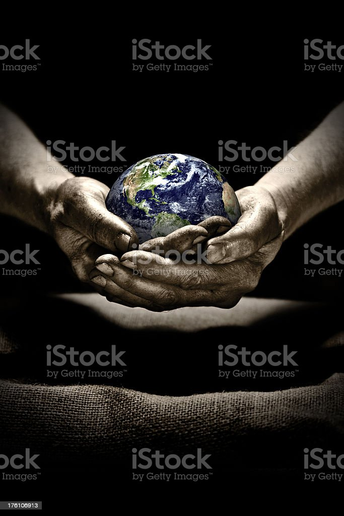 \'Dirty hands carefully holding globe in spotlight. Conseptual image:...