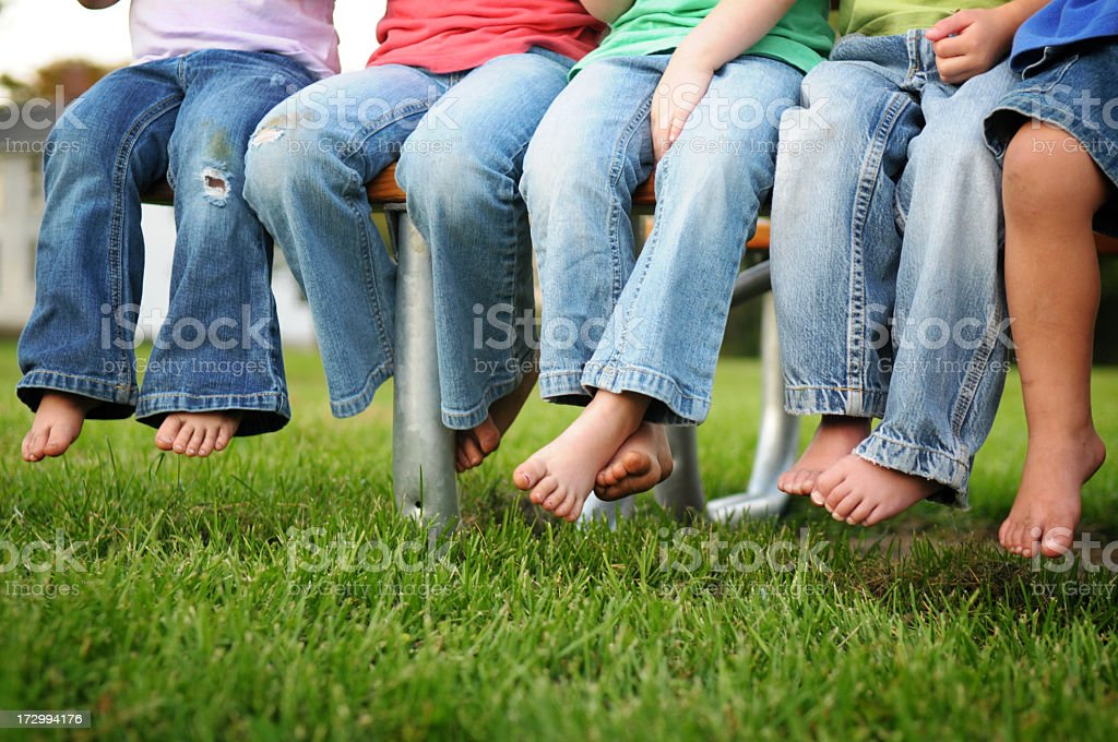 Dirty Legs and Feet of Children Sitting on a Bench royalty-free stock photo