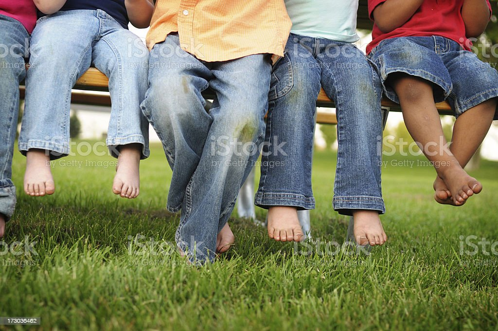 Dirty Legs and Feet of Children Sitting on a Bench stock photo