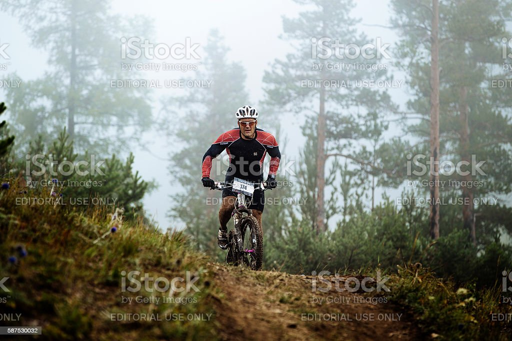 dirty male cyclist rides along top of hill royalty-free 스톡 사진