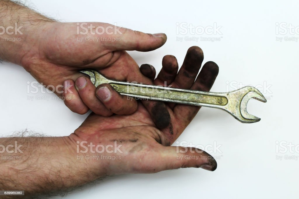 Dirty man's hand with a metal wrench stock photo