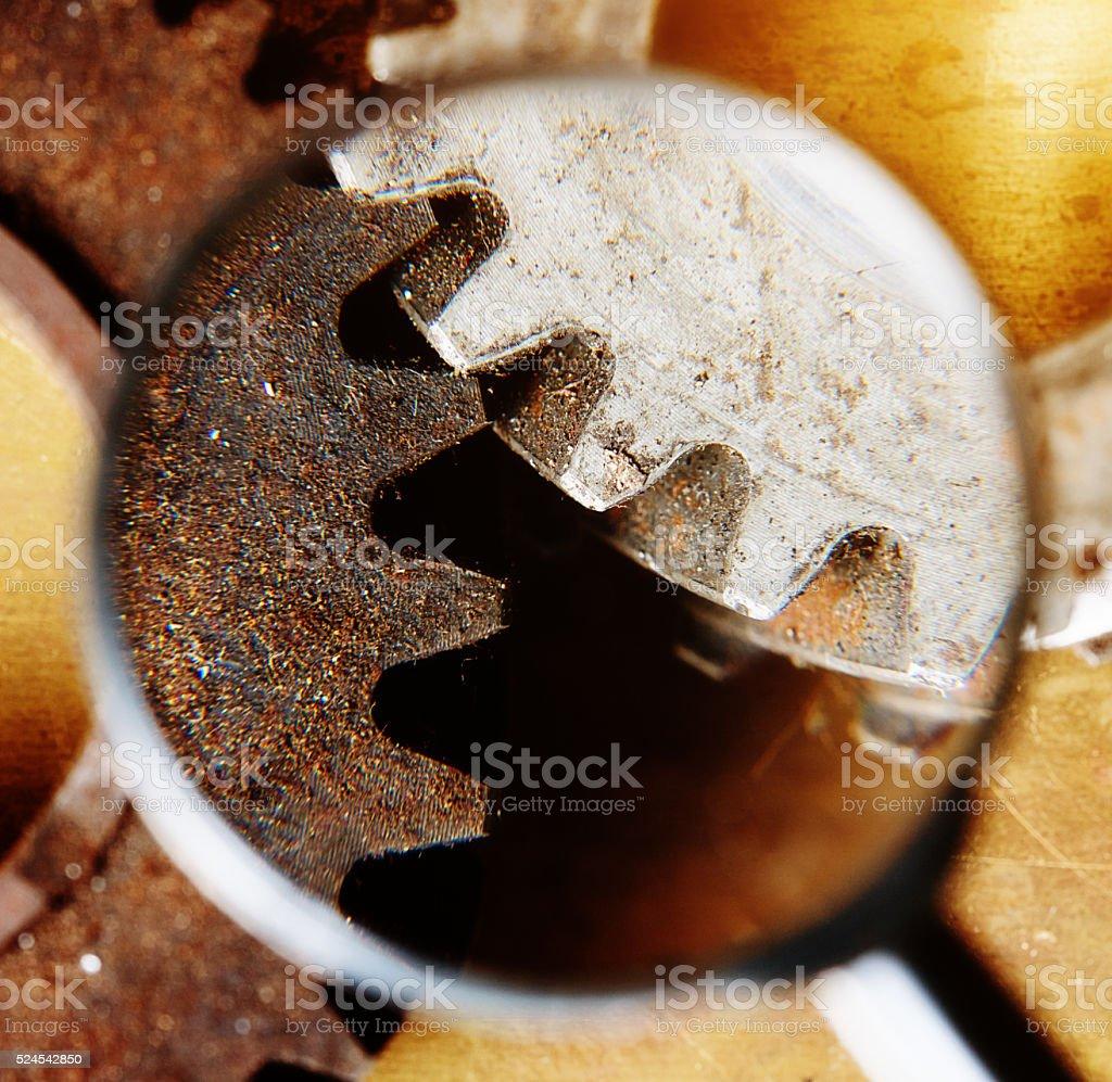 Dirty meshing gears seen through magnifying glass. stock photo
