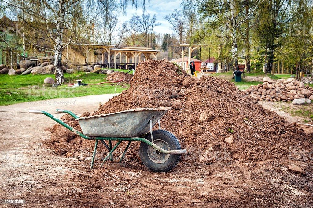 Dirty metal garden wheelbarrow on the bare ground stock photo