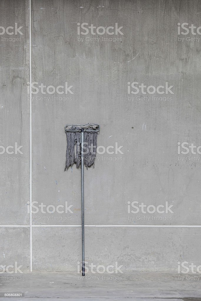 dirty mop leaned on the cement wall stock photo