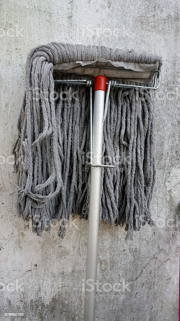 Dirty mop on wall background stock photo