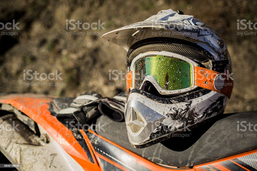 Dirty motorcycle motocross helmet with goggles stock photo