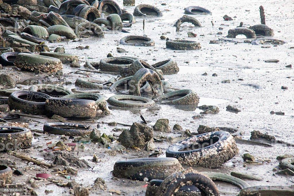 Dirty muddy beach showing a dump site stock photo