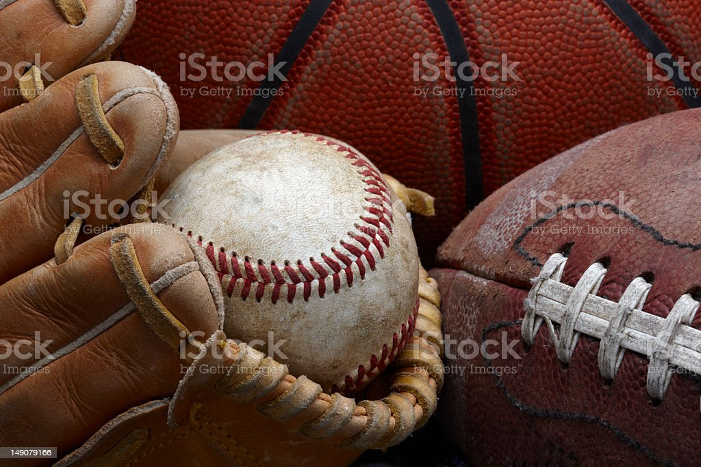 Dirty old baseball, glove, football and basketball stock photo