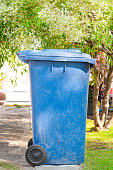 dirty old blue bin with wheel  in the park
