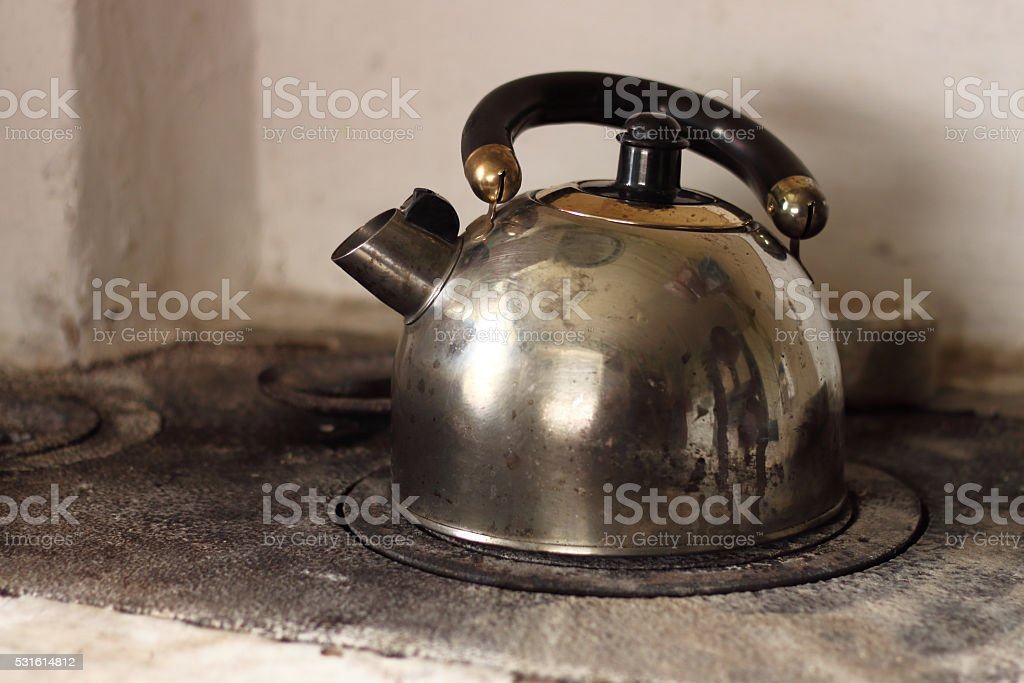 Dirty old kettle is boiling on firewood stove. stock photo