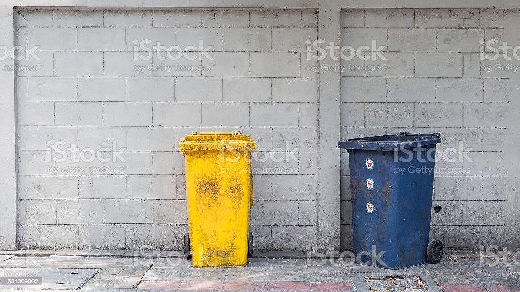 Dirty plastic trash bin with wheels on footpath stock photo