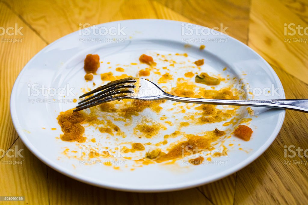 Dirty plate with a fork in  restaurant stock photo