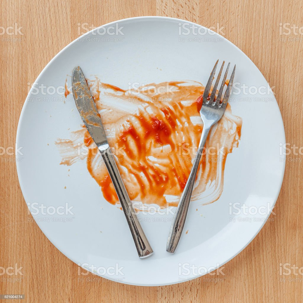 Dirty plate with knife and fork smeared with tomato sauce. stock photo