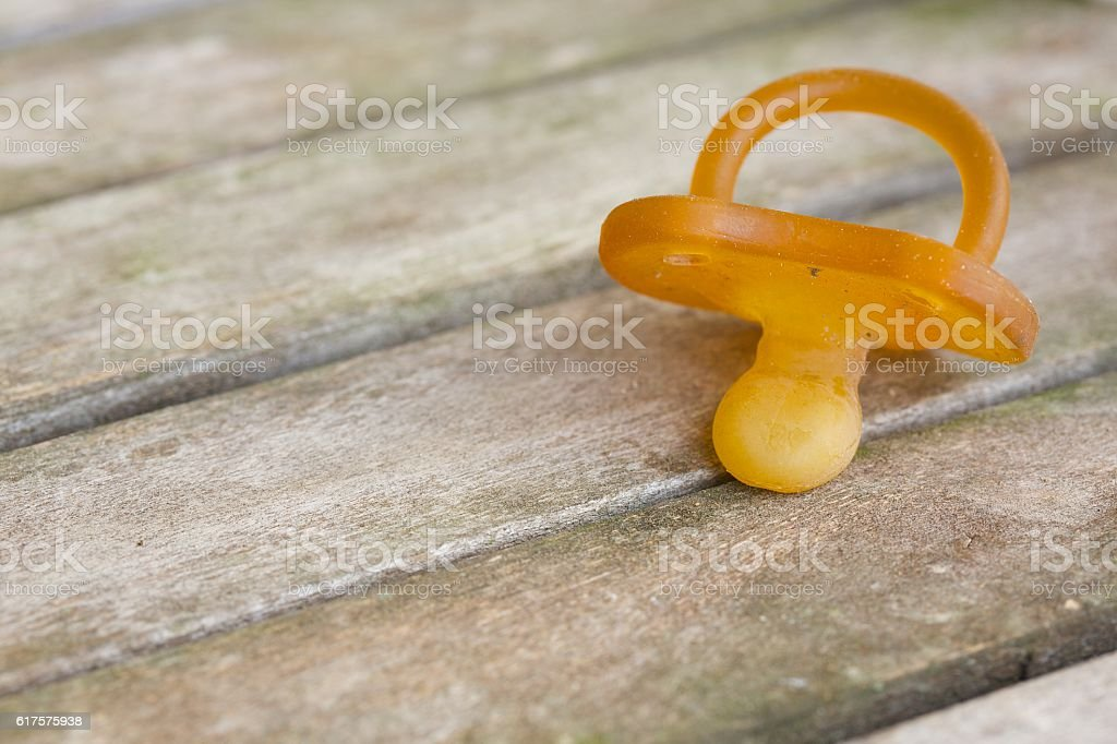 Dirty rubber pacifier on a wooden surface. Closeup stock photo