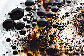 Dirty Tar balls from enviormental oil spilled in clear water