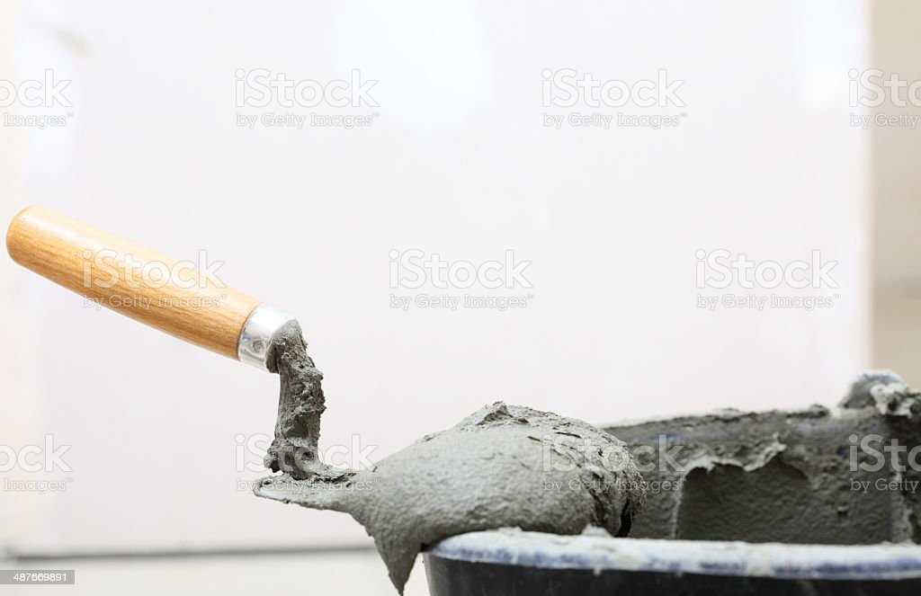 Dirty trowel and bucket on building site. Renovation at home stock photo