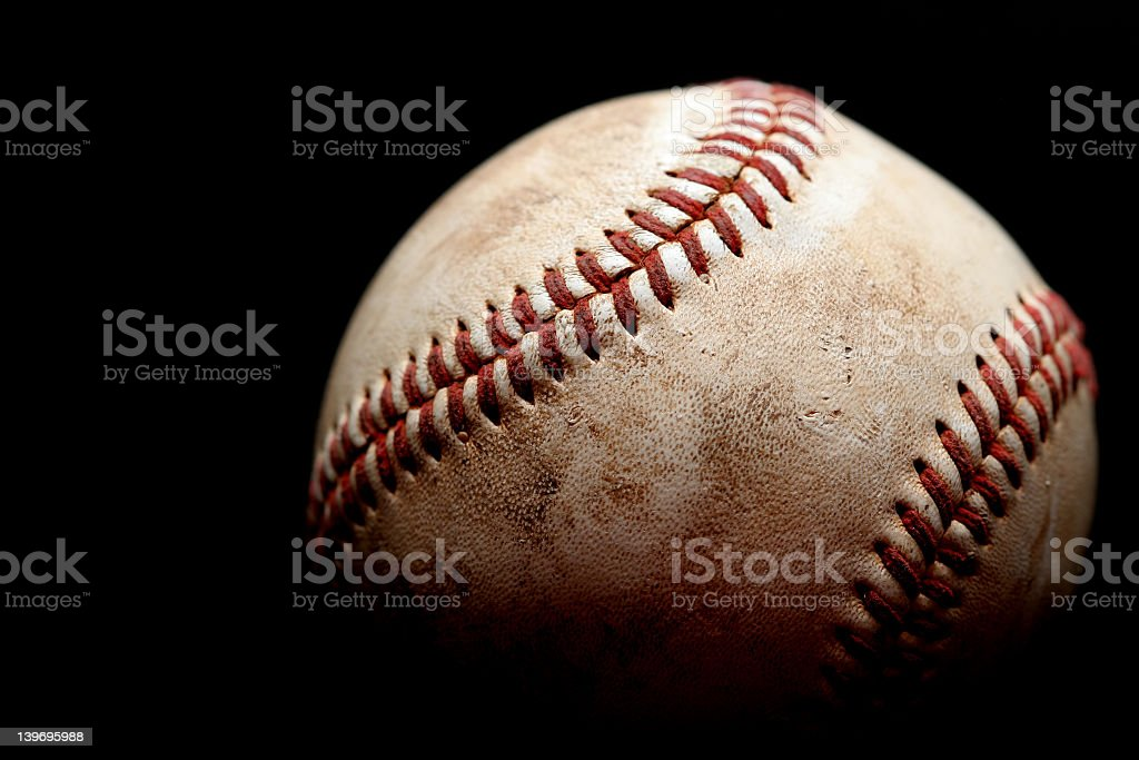 A dirty, used baseball with a black background stock photo