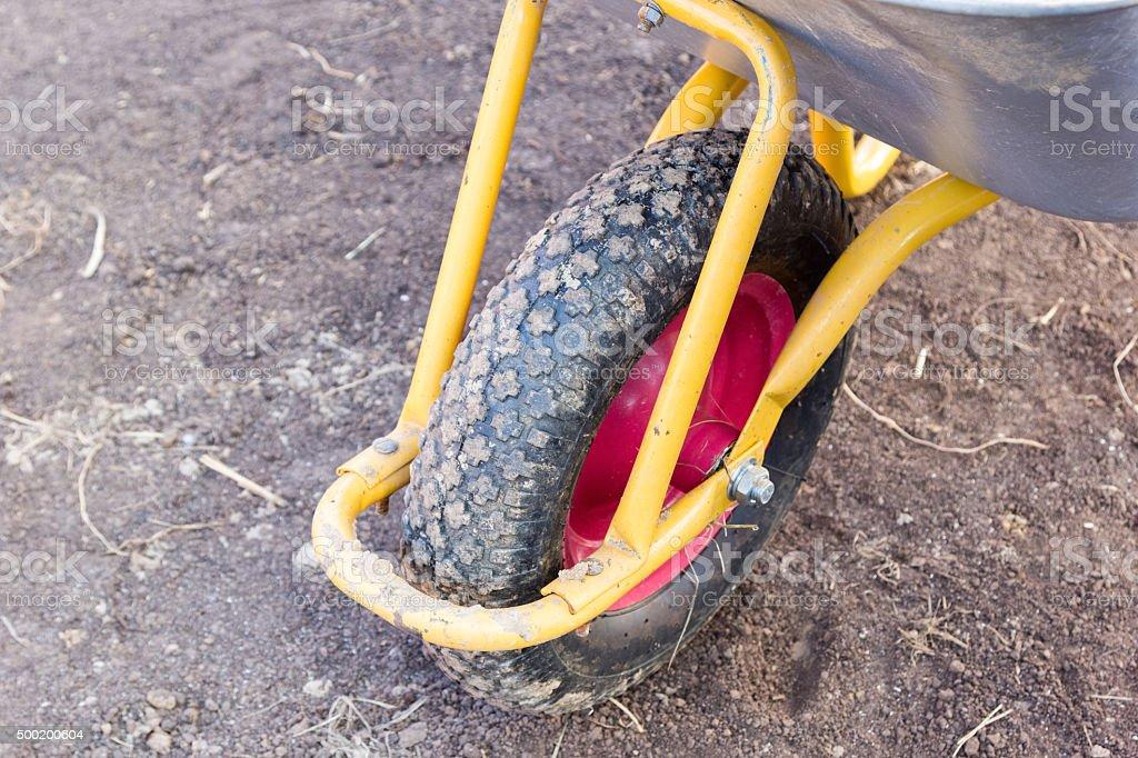 dirty wheelbarrow wheel on bare ground stock photo
