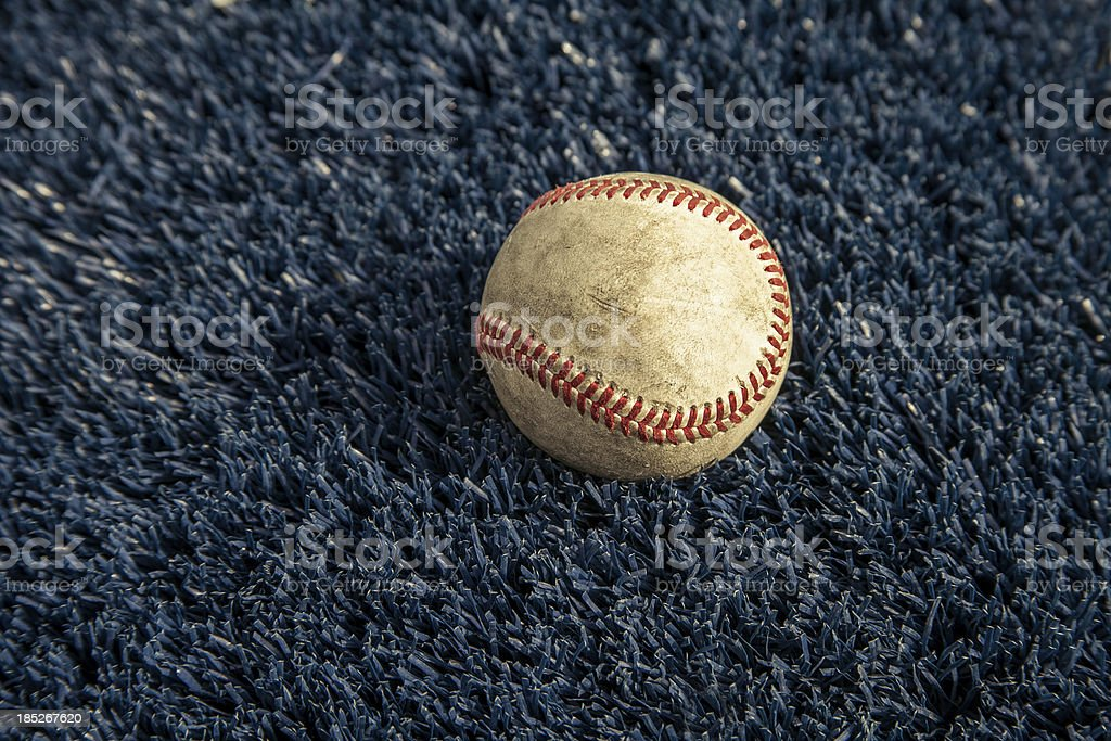 Dirty White Baseball with Red Stitching on Blue Carpet, Closeup stock photo