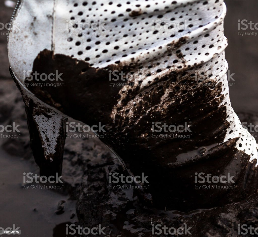 Dirty white high-heel shoe in the mud stock photo