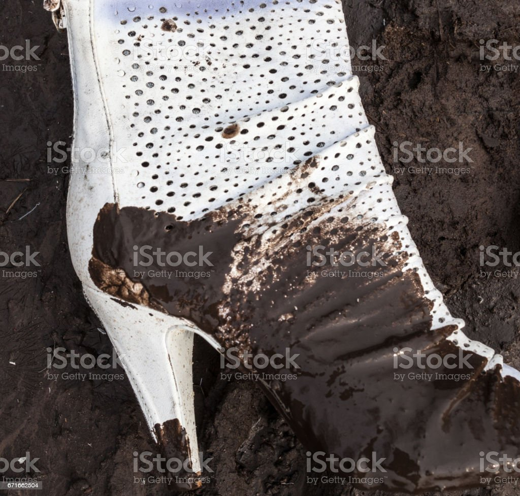 Dirty white high-heel shoe on the ground stock photo