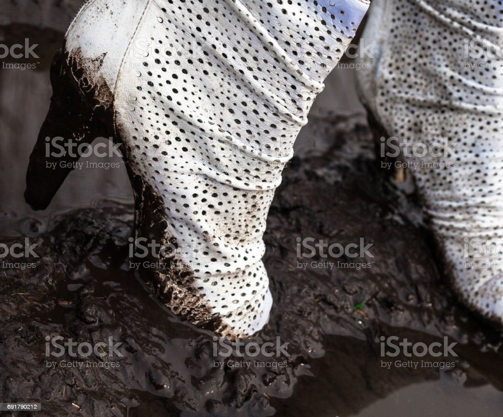Dirty white high-heel shoes in the mud stock photo