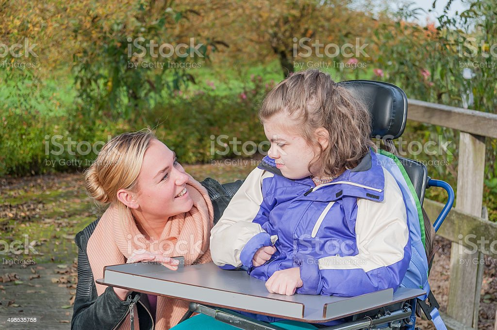 Disability a disabled child in a wheelchair relaxing outside stock photo