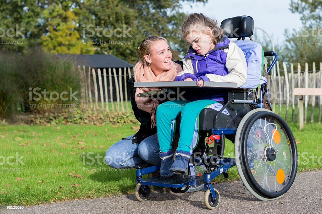 Disability a disabled girl in a wheelchair relaxing outside stock photo