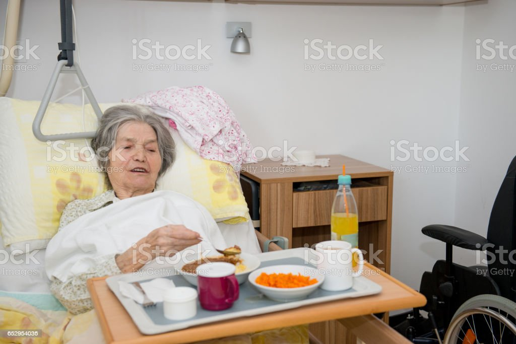 Disable Senior Woman Having Lunch In Her Bed stock photo