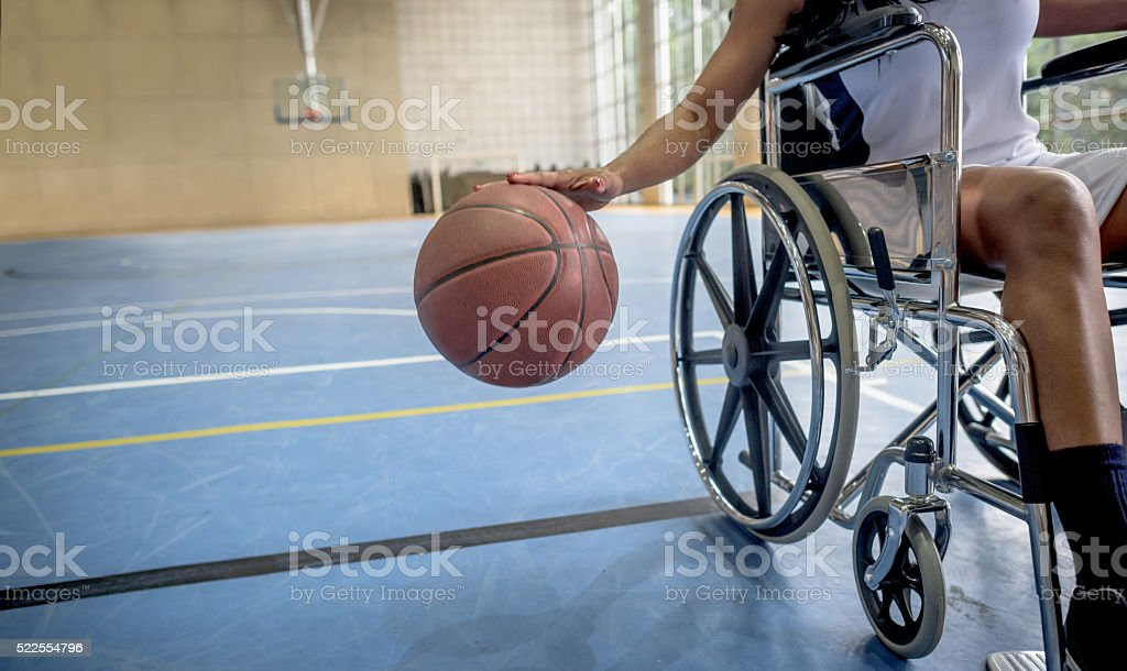 Disabled basketball player bouncing the ball stock photo