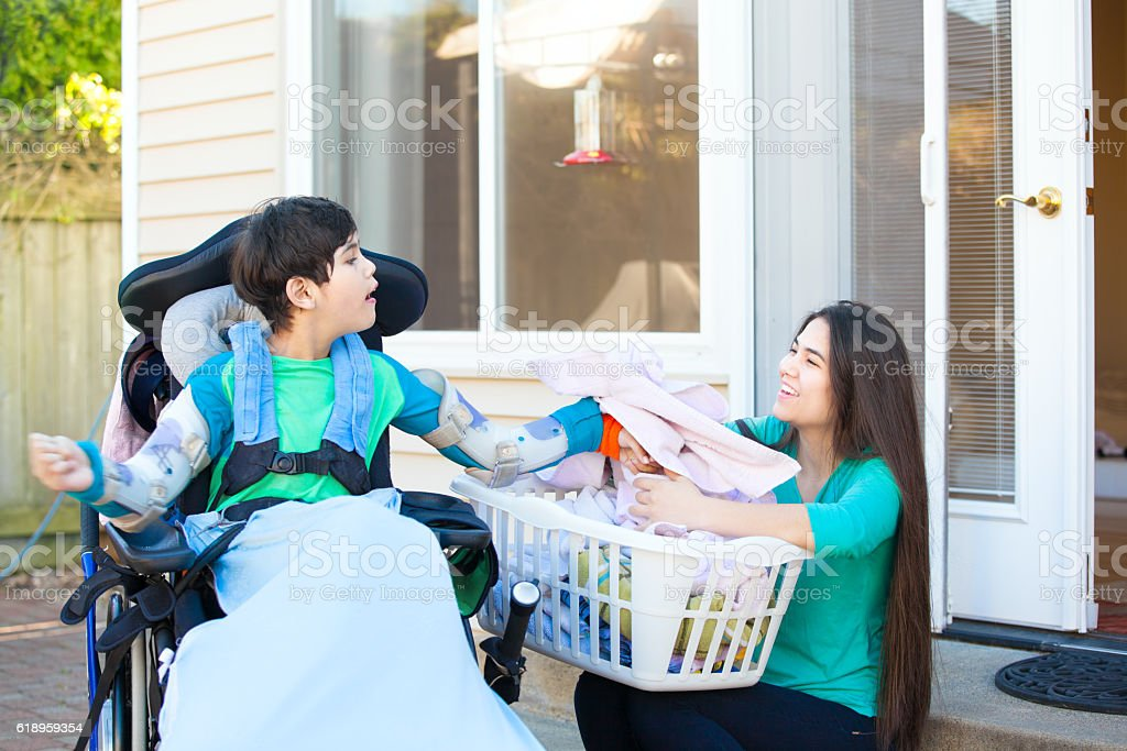 Disabled boy in wheelchair helping older sister fold laundry stock photo